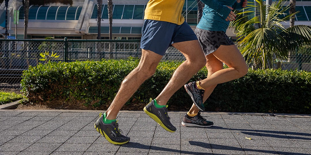 Two People Running Side-by-Side In The City
