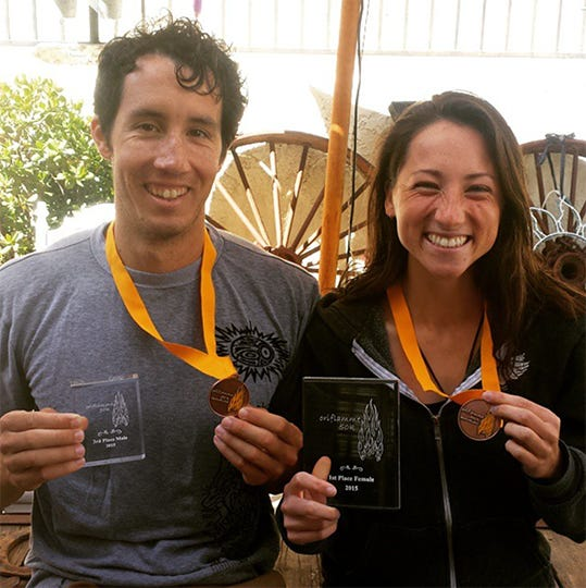 Jade Belzberg with her husband, holding up their medals and trophies